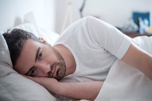man lying in bed staring into space, depression therapy